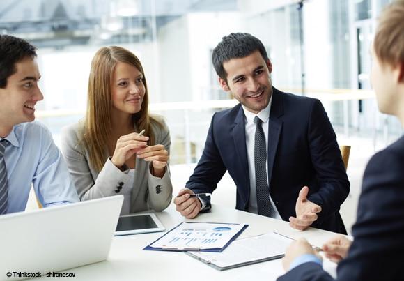 des personnes en costume-cravate et tailleurs discutent autour d'une table avec ordinateur, tablette et documents