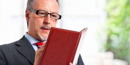 cliché de l' inspecteur du travail :un homme en costume cravate et lunettes prend des notes dans un carnet relié