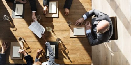 vue de haut de plusieurs personnes avec papier et crayon réunies autour d'une table
