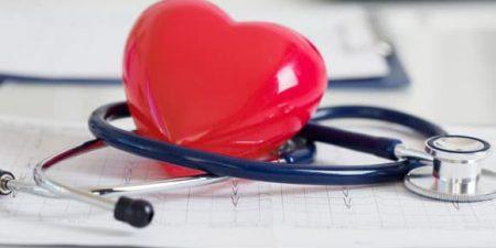 un cœur en plastique entouré par un stethoscope de médecin
