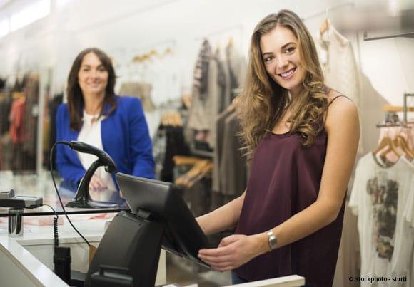 une jeune femme tient la caisse d'un magasin de vêtement