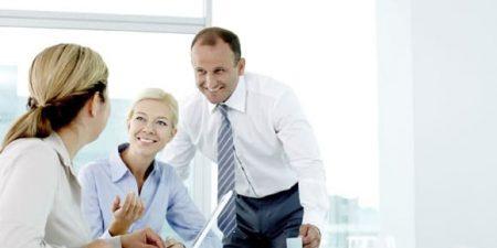 Dans un environnement de travail, un homme discute avec deux femmes