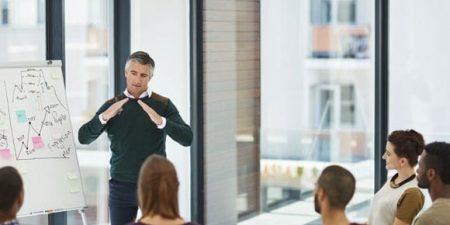 Un homme debout devant un paperboard en pleine explication face à un public d'adultes