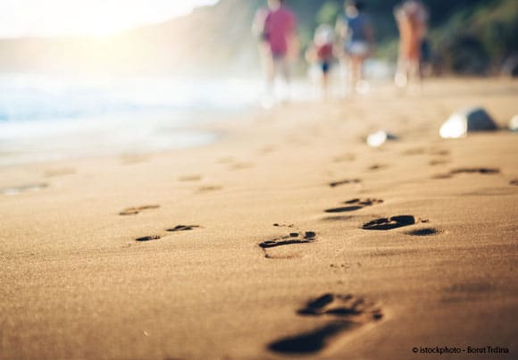 gros plan sur une plage de sable que des promeneurs en second plan ont foulée