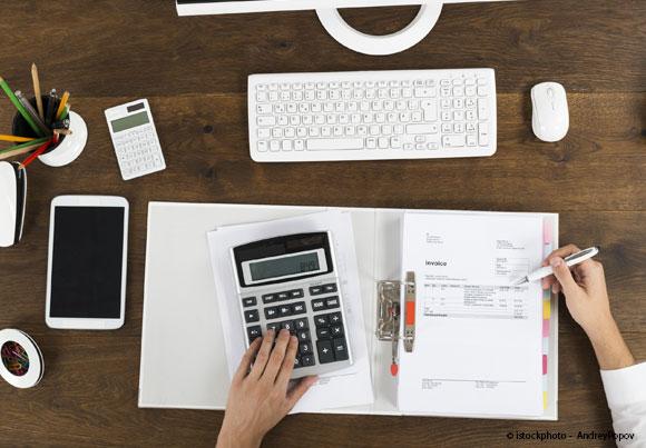 cahier de compte, calculette et smartphone avec deux mains