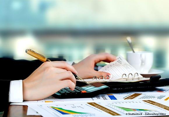une main équipée d'un crayon, avec une calculette et un agenda à côté