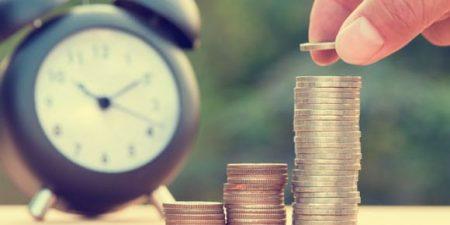 un réveil et une pile de pièces de monnaie