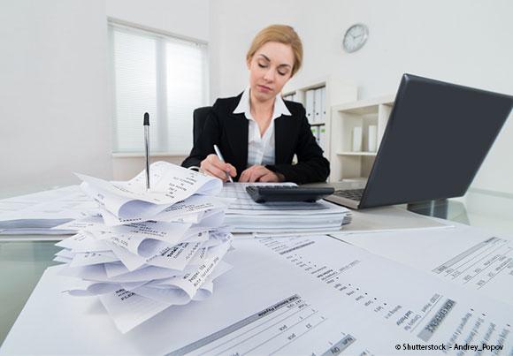 tickets et factures en premier plan, une femme avec une calculette et son
