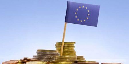 des pièces de monnaie et un drapeau européen