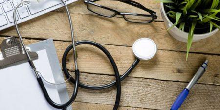 un clavier d'ordinateur, des lunettes, un stéthoscope