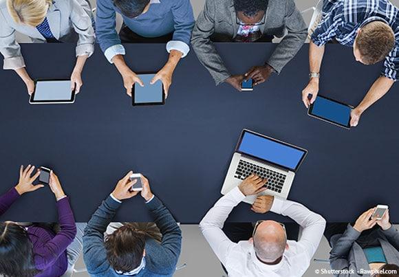 des personnes autour d'une table utilisent smartphones, tablettes, et ordinateurs évoquant l'utilité d'une charte informatique