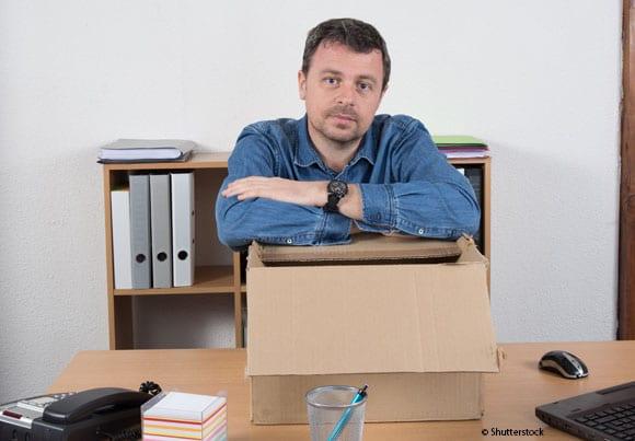 un homme accoudé à un grand carton posé sur un bureau comme s'il était licencié pour maladie