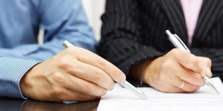 deux mains équipées de stylo posées sur une document