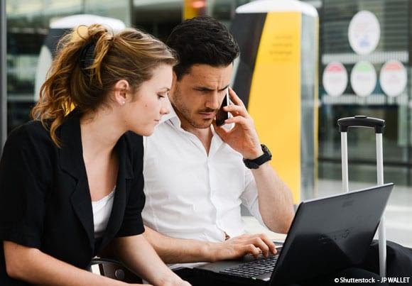 Deux personnes consultent un ordinateur dans un hall de gare
