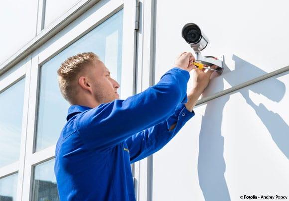 un homme en bleu de travail installe une caméra extérieure