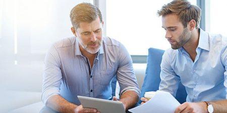 Deux hommes, l'un jeune l'autre senior, discutent, avec des documents en main