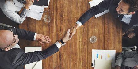 Deux mains de part et d'autre d'une table se serrent en symbole de la transmission d'entreprise à un associé