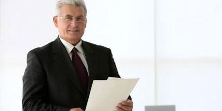 Un sénior dans un bureau pour évoquer la question psychologique de la cession d'entreprise
