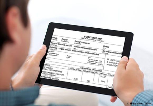 quelqu'un consulte sur une tablette son bulletin de paie